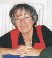 <b>Hannelore Hinz</b> sitting at a desk smiling - hanne04
